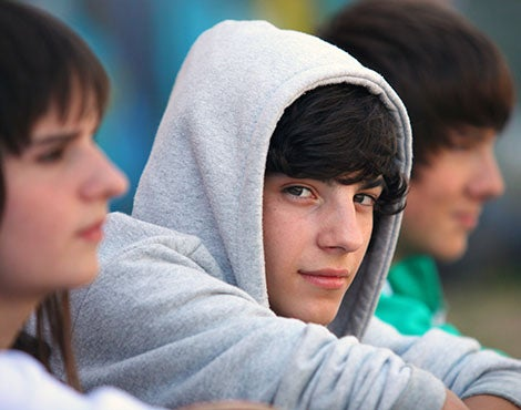 Young man perhaps high school or college age with a heather gray sweatshirt hoodie  pulled over his head looking at you.