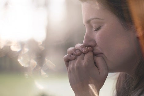 Young lady holding hands together up to mouth with closed eyes thinking.