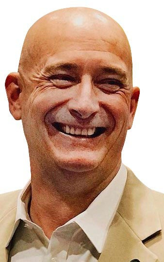 Man with bald head and tan jacket smiles.