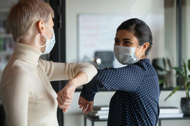 Two women bump elbows while wearing masks.
