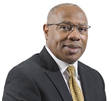 African American man in dark suit with gold tie and glasses.