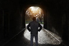 A man stands in a tunnel looking toward the light at the end which appears to open up into a forest-like park.