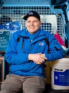 Matt Amendt sitting in the back of a work van smiling at the camera wearing a bright blue work jacket and baseball cap.
