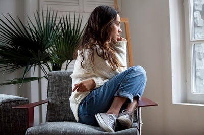 A young woman with brown wavy hair who is sitting on a chair with her legs drawn up to her chest while sadly gazing out a window.