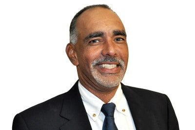 Man with brown skin and graying hair wearing a tie smiles at camera.