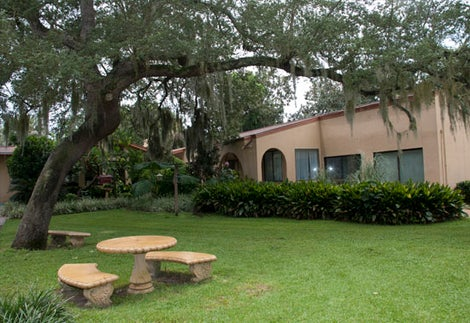 The Friary at Lakeview Center courtyard with benches, trees and Friary building.