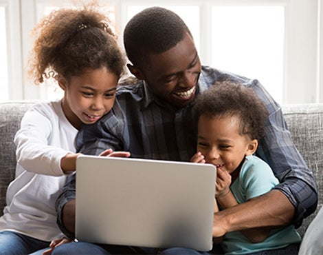 A black father laughs with two children on laptop.