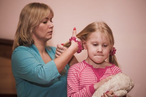 A women brushes a young girl's hair who has a determined look on her face, possibly reflecting on a bad memory.