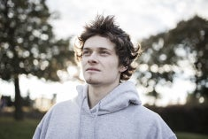 A pale-faced young man with messy hair wearing a grey sweatshirt looking up and away toward something hopeful.