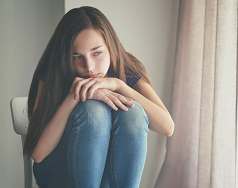 A female teen sits with chin to knees looking solemn.
