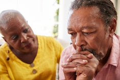 An older African american man resting his chin in his hands looking anxious and worried, a women (perhaps his wife) leans in to show concern.