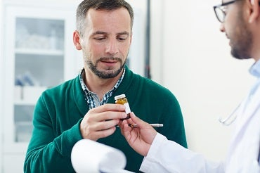 Man in his 30s take s prescription pill bottle from a physician in a white coat and glasses.