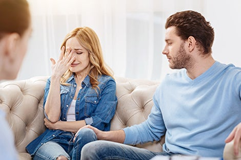 A young woman cries while her spouse looks on comforting.