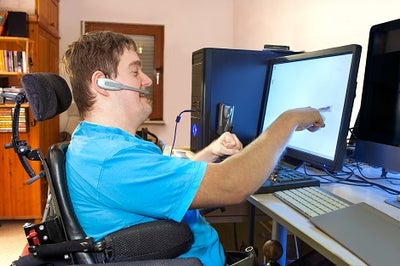 A younger man sitting in a wheelchair at his desk pointing at a computer screen.