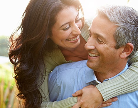 Woman hugs a man and both are smiling.