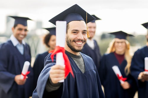 Graduate hold up certificate and smiles.