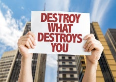 Person holding a sign in front of a tall building that reads Destroy What Destroys You.