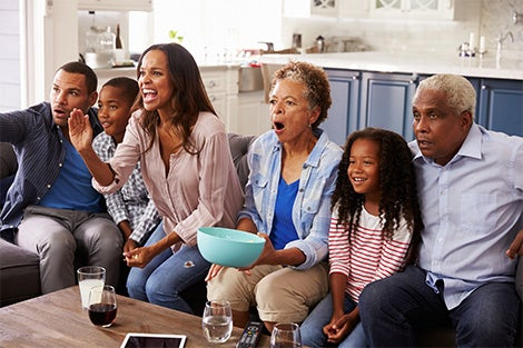 Family enjoys watching a TV program - perhaps rooting on their favorite sports team.