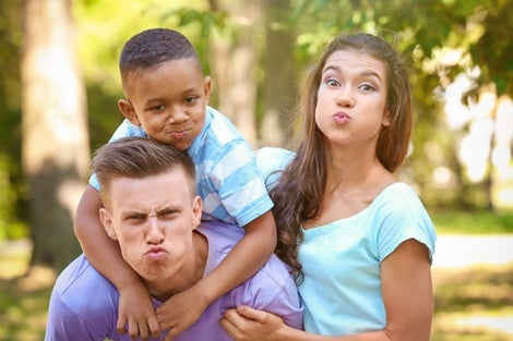 A young caucasian couple, makes funny faces with a young African American boy about 10 years old, being silly.
