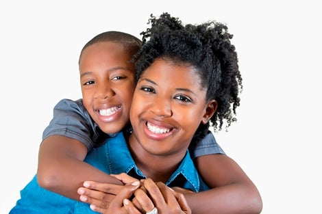 This photo depicts a young boy and woman embracing and smiling.