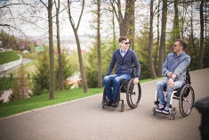 Two young men in wheelchairs rolling through park while laughing and talking.