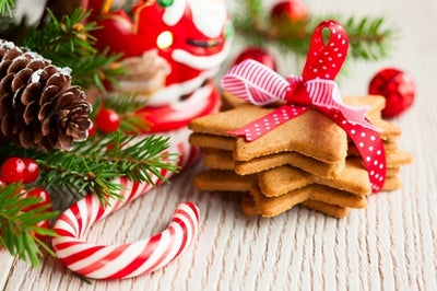 Image of candy cane, Santa ornament and stack of ginger bread cookies shaped like stars.