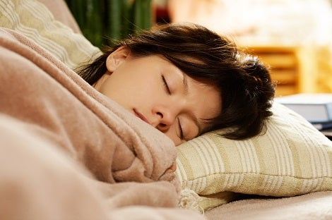 A young woman with brown hair is under a blanket with her head on a pillow asleep.