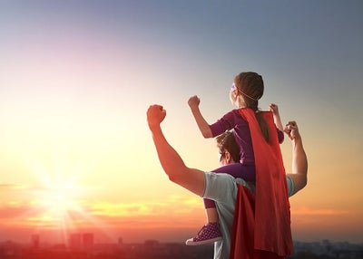 A father and son with superhero capes posing with arms up and looking toward the bright sun.