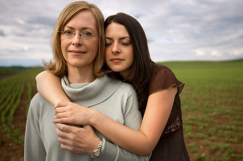A brown-haired young woman embraces an older woman with light hair.