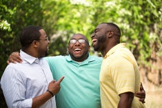 Three African american men embracing a moment of laughter as they smile big.