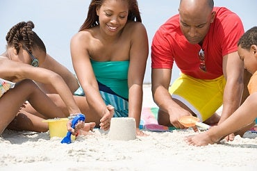 An African American man, woman and two children playing at the beach in the sand.