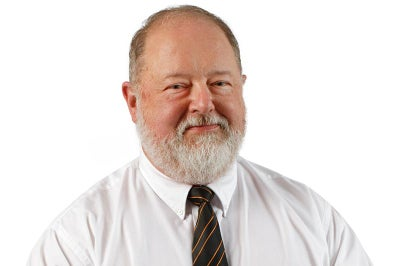 Man with beard wearing a tie smiles at camera.