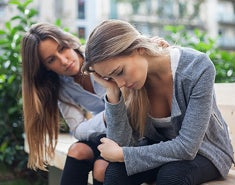 A young woman comforts a depressed female friend.
