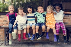 A diverse group of young kids around the age of 7 laughing with each other while sitting on a bench.