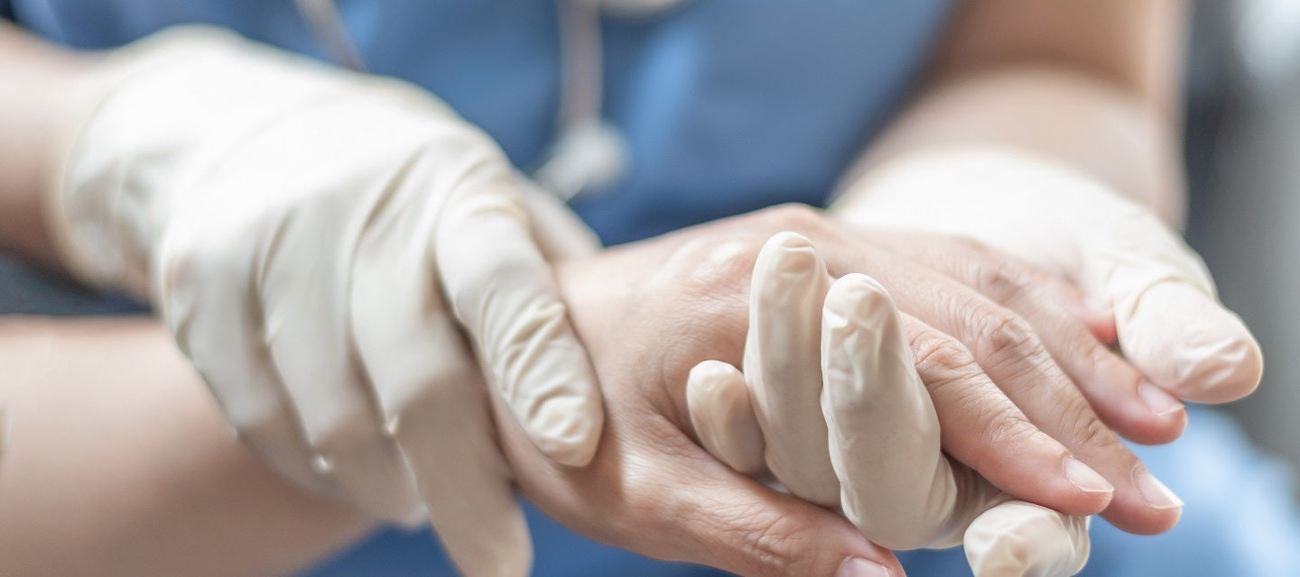 Nurse with gloved hands holding patient's hand