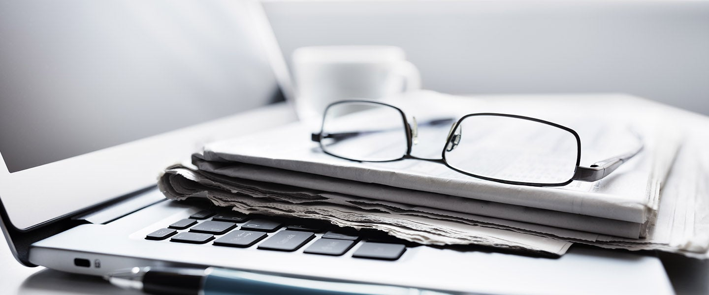 Glasses and newspaper on laptop
