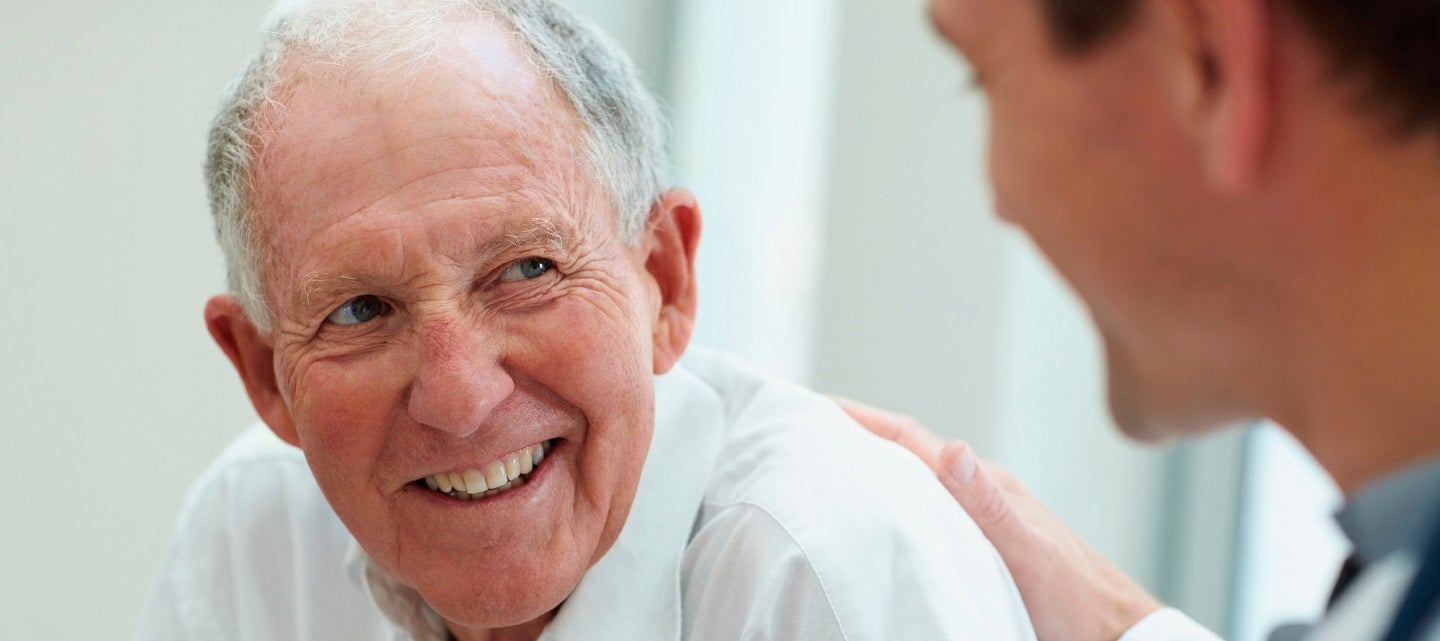 Older man being reassured by younger doctor