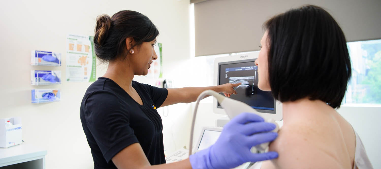 A sonographer scanning a woman's shoulder