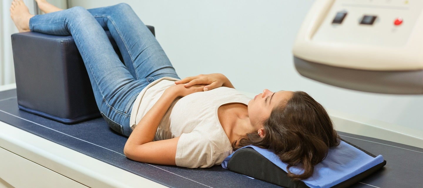 Woman lying on bone densitometry scanner