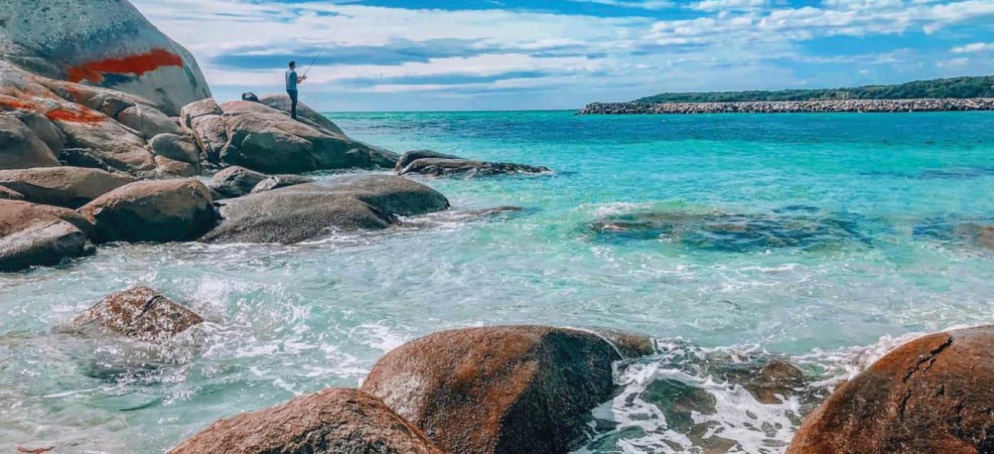 Man standing on rocks next to ocean fishing