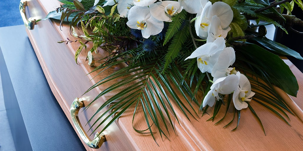 wood coffin with white flowers on top