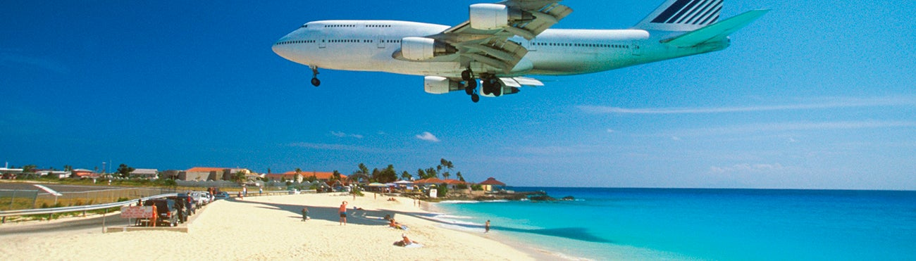 Airplane travelling over vacation beach