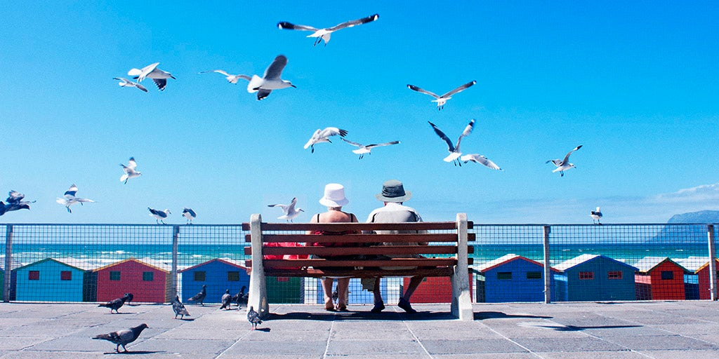 Senior Citizens with over 50s life insurance sitting along the beach