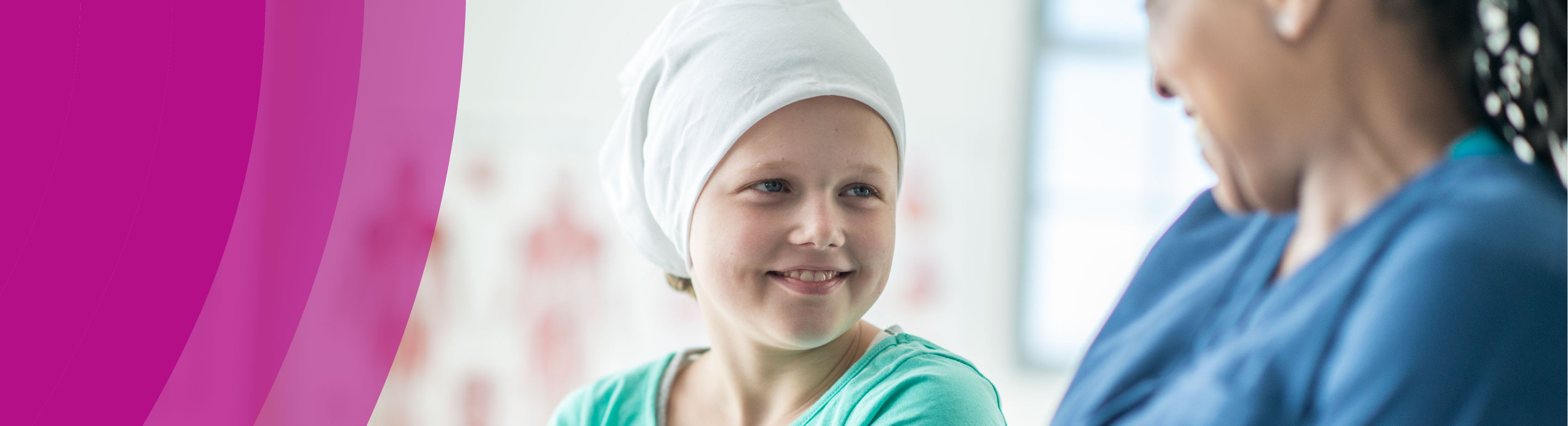 healthcare worker and child with head-wrap smile at each other
