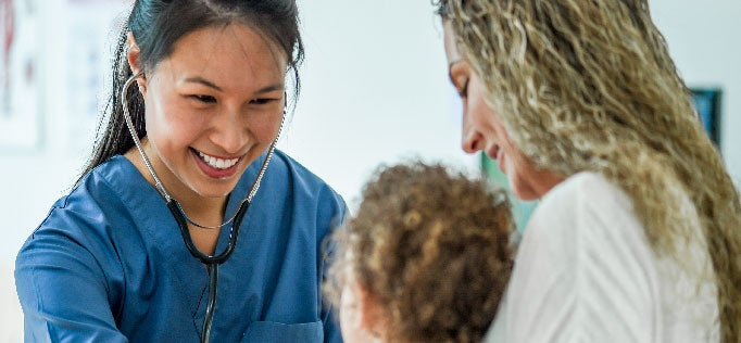 smiling healthcare worker examines child with mother
