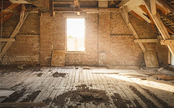 an attic with a window and sun shining in