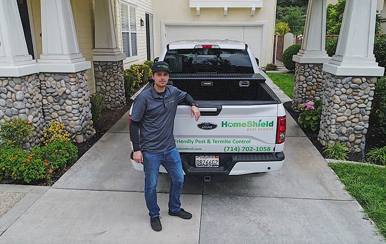 technician standing with a company truck