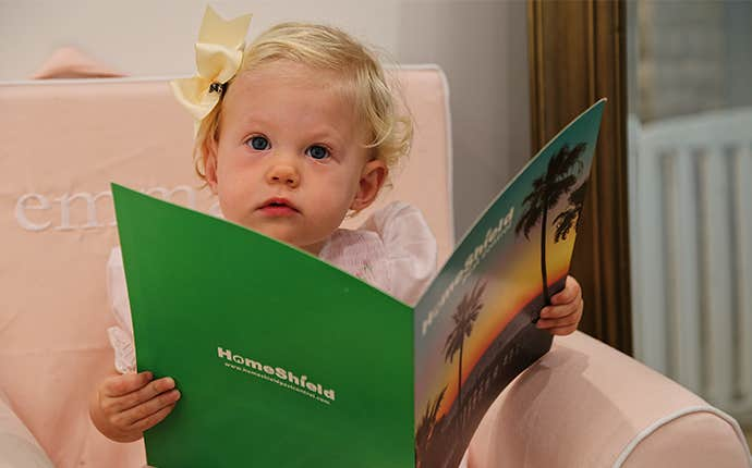 a small child holding a homeshield folder
