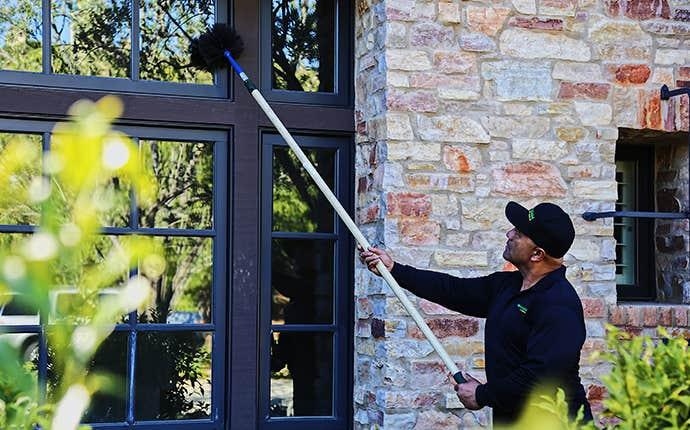 a technician dewebbing an exterior window