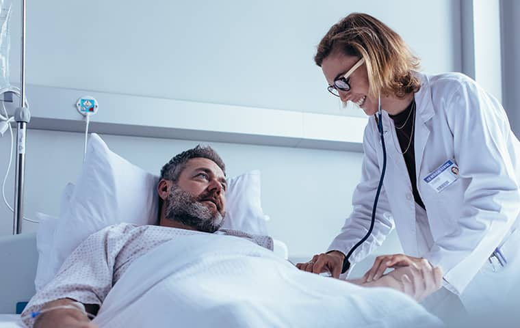 a female doctor checking in on a male patient